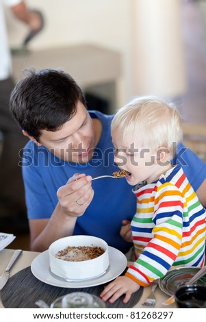 father and his son having a delicious breakfast together - stock photo