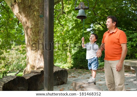 Father and his son having a got time in the park. Little boy is ringing a bell. - stock photo