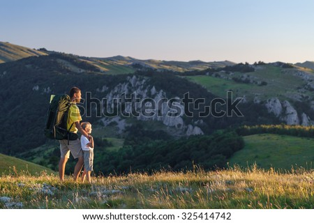 Father and his son hiking at mountains in the summer