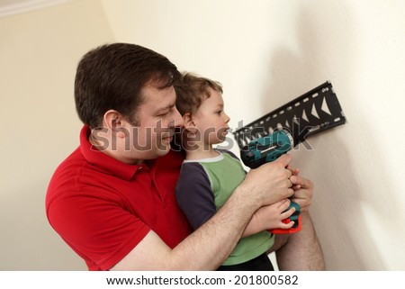 Father and his son installing mount TV on the wall at home - stock photo