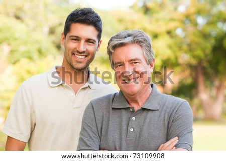 Father and his son looking at the camera - stock photo