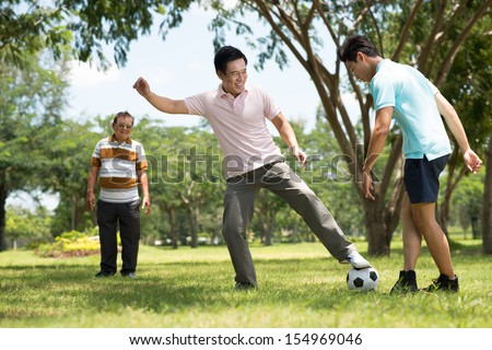 Father and his son playing football while the grandfather looking at them on the foreground - stock photo