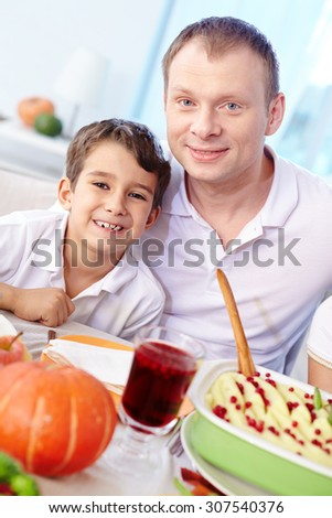 Father and his son sitting at dining table - stock photo