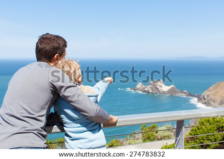 father and his son using binoculars together and enjoying the view of california coast - stock photo