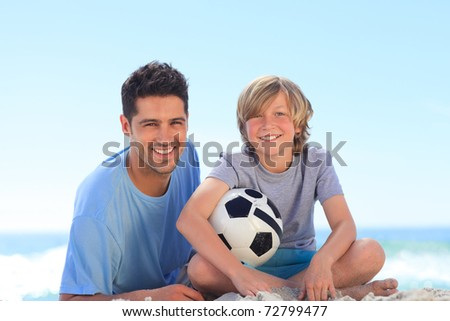 Father and his son with a ball - stock photo