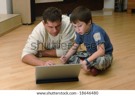 Father and his son with laptop on a floor