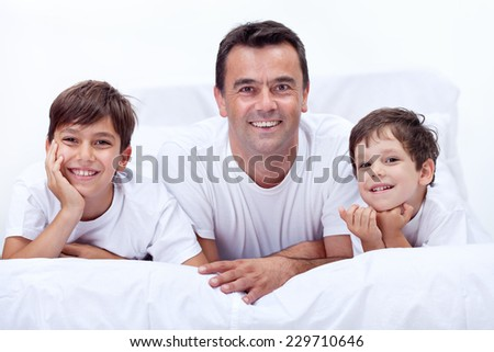 Father and his sons having boys time together on a lazy morning - stock photo