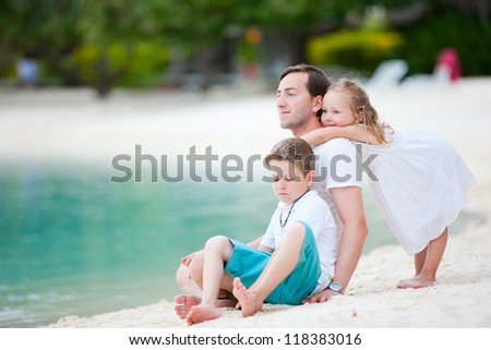 Father and his two kids enjoying tropical beach vacation - stock photo