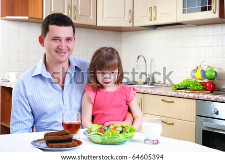 Father and his young daughter eat breakfast together in his kitchen.