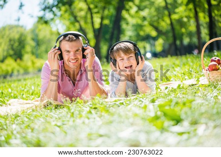 Father and kid in summer park enjoying music - stock photo