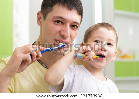father and kid son brushing teeth together in bathroom - stock photo