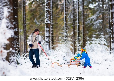 Father and kids enjoy a sleigh ride in winter forest. Baby boy and toddler girl sled in snowy park. Dad pulling children on sledge. Parent and child sledding. Family outdoor fun on Christmas vacation - stock photo