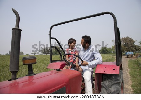 Father and little boy looking at each other while sitting in a tractor