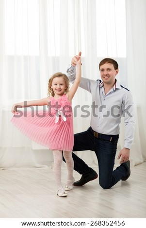 Father and little daughter dancing. Little princess in pink dress walking around dad standing on knee