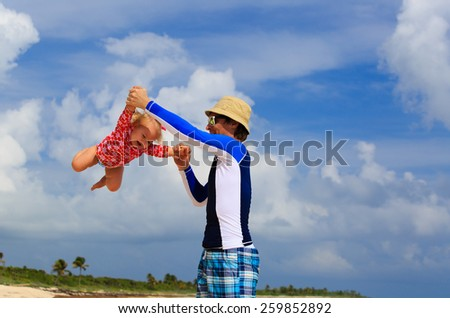 father and little daughter having fun on summer sky - stock photo