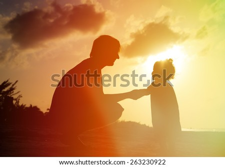 Father and little daughter silhouettes  holding hands at sunset