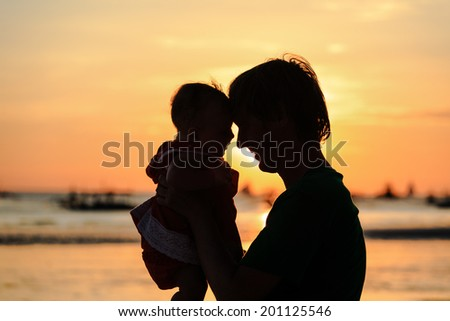 Father and little daughter silhouettes on beach at sunset