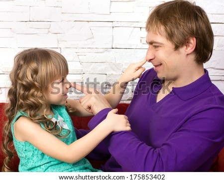 father and little daughter sitting on red sofa  on modern background  looking at each other and  playing