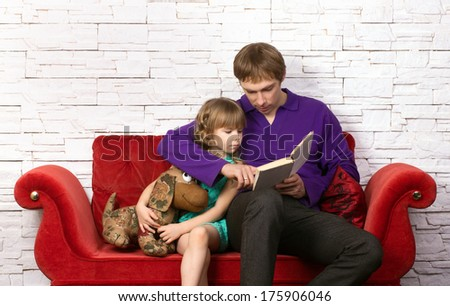 father and little daughter sitting on red sofa with toy and book on modern background  - stock photo