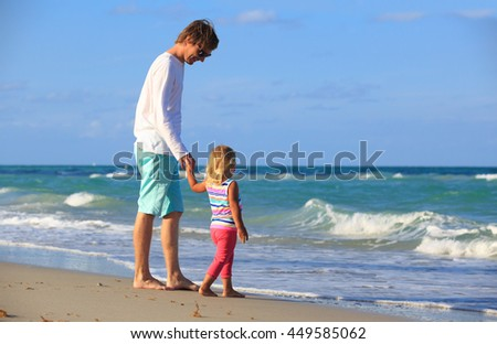 father and little daughter walk at beach