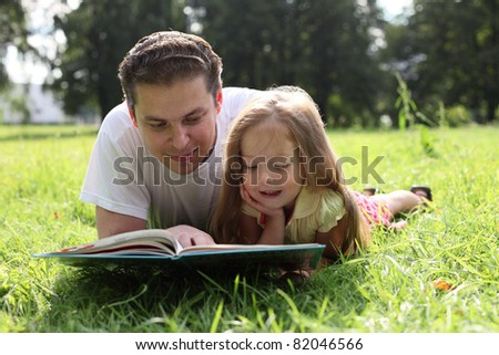 Father and little girl reading book together - stock photo