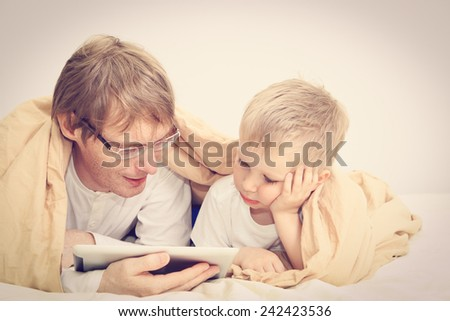 father and little son looking at touch pad in bedroom