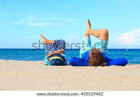 father and little son play on beach