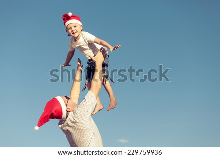 Father and little son playing near a house at the day time. Concept of friendly family. - stock photo
