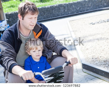 Father and little son playing together outdoors on toy car in summer - stock photo