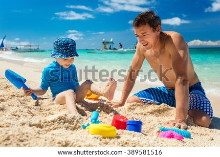 Father and little son playing with sand on the beach - stock photo
