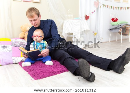 Father and little son read an old book sitting on the carpet - stock photo