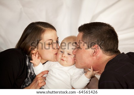 father and mother kissing their baby girl