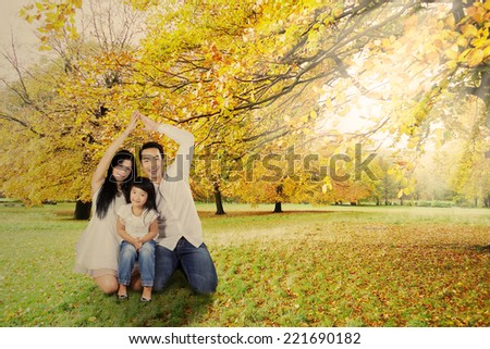 Father and mother made a home shape with their hands to protect their child - stock photo