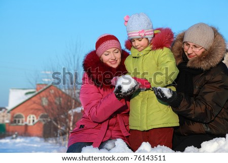 father and mother offer to daughter to make snowball outdoors in winter near house - stock photo