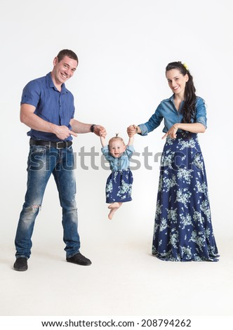 Father and mother rocking her daughter in her arms like on a swing - stock photo