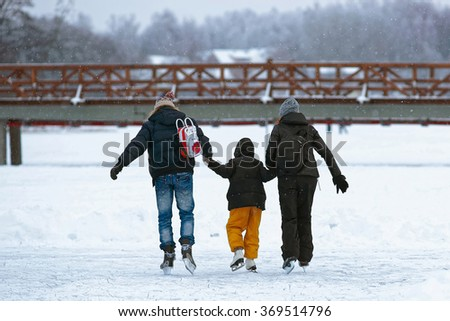 Father and mother teaching kid to skate on the rink in winter. Skating involves any sports or recreational activity which consists of traveling on surfaces or on ice using skates. Selective focus - stock photo