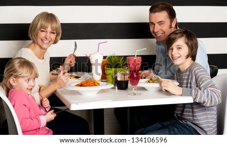 Father and mother with children enjoying meal in restaurant. - stock photo