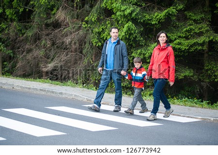 Father and Mother with their Son crossing the Road - stock photo