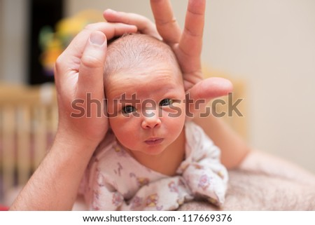 Father and newborn baby cuddling at home - stock photo