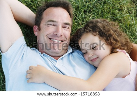 Father and sleeping daughter lying outdoors smiling - stock photo