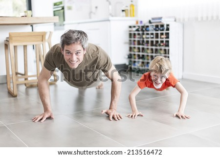 father and son  are doing push-ups and having fun  at home - stock photo