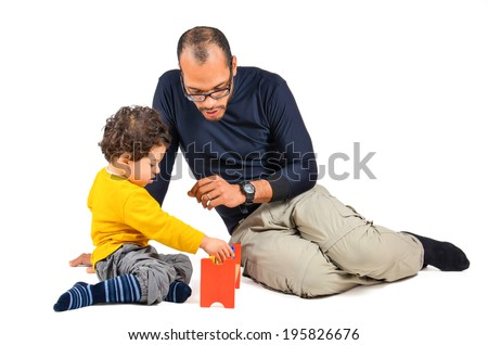 Father and son are playing together as part of the didactic children therapy. A therapist is working with little child. Didactic therapeutic toys for autism.   - stock photo