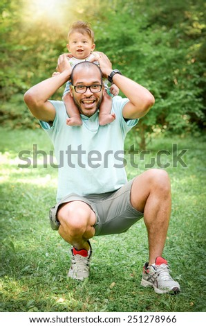 Father and son are playing together in a park. Happy single parent enjoying time with his son - stock photo