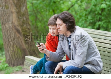 father and son are sitting on a Park bench with a smartphone - stock photo