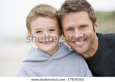 Father and son at beach smiling - stock photo