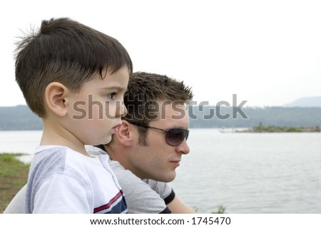 Father and son at lake. - stock photo