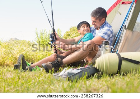 Father and son beside their tent on a sunny day - stock photo