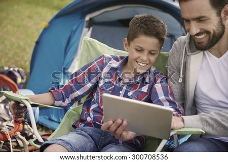 Father and son browsing the Internet on the camping