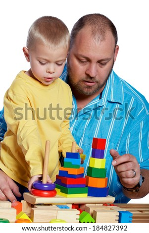 Father and son building blocks on white studio background - stock photo