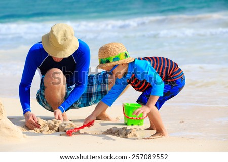 father and son building sand castle on tropical sand beach - stock photo